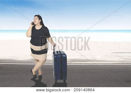 Portrait of a fat young woman speaking on a mobile phone while standing on the beach with a suitcase