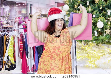 Image of fat woman looks happy while carrying Christmas gifts and standing in the mall