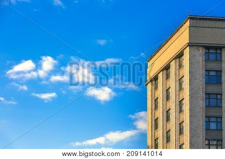 The building of classical architecture strict and restrained facing the walls with light limestone. A bright blue sky with small clouds. Copy space for text. Skyscraper, Moscow, Russia.