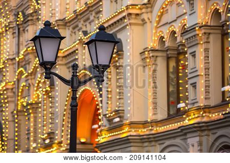 Street black lamppost Pushkin with a lamp made of cast iron against a background of a beautiful building decorated with luminous garlands for the Christmas holidays. City lamppost, Moscow, Russia.