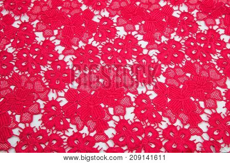 bright crimson, red guipure smoothly laid out on a white table