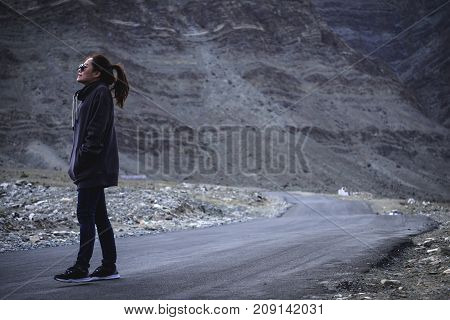 Portrait image of a beautiful Asian woman tourist standing and walking on the road in front of mountain background