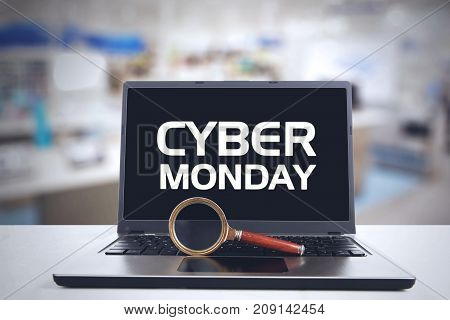 Cyber Monday Concept. Magnifying glass and Cyber Monday text on the laptop computer above desk