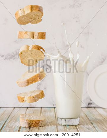 Bread And Milk. Flying Baguette And Milk Splash In A Glass