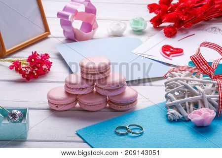 Pink heart shaped macaroons and wedding rings with postcard. place for inscription. valentine's day