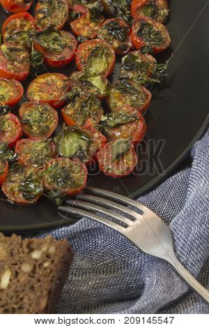 Cherry tomatoes baked in the oven with basil