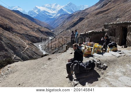 NEPAL. MANANG - NOVEMBER 16 2016 : Tourist trekker near a small shop high in the mountains on the trail around Annapurna. Manang largest alpine tourist town on the Annapurna Circuit.