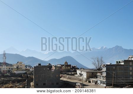 NEPAL. MUKTINATH - NOVEMBER 18 2016 : View of Muktinath in the background of the silhouette of the Himalayas and Mount Nilgiri. Muktinath is an ancient city in the Himalayas with a great religious and tourist significance for Nepal.
