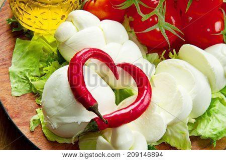 a fresh italian mozzarella with tomato and salad