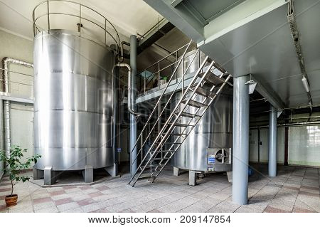 Two metal tanks installed inside the building. Equipment for mixing sugar and yeast mixture.
