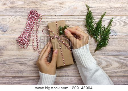 Woman wrapping presents for Christmas. Hands of woman decorating Christmas gift box.