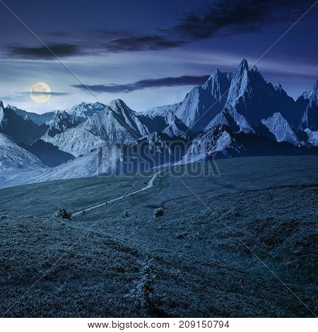 grassy slopes and rocky peaks composite. gorgeous summer landscape with magnificent mountain ridge over the pleasing green meadows. lovely surreal fantasy scenery at night in full moon light