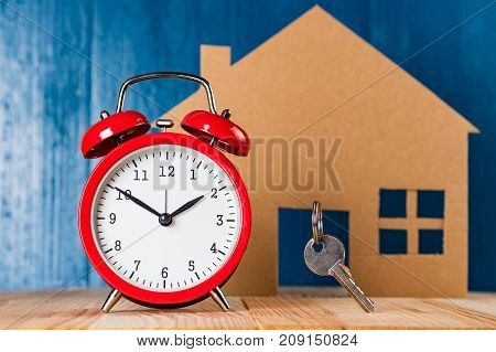 Old vintage alarm clock and door key against house shape and blue background. Time to buy a home abstract concept.