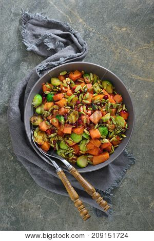 Butternut squash and brussels sprouts salad with cranberry and pumpkin seeds simple holiday Thanksgiving side dish overhead view