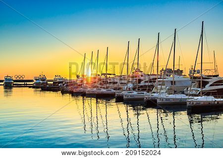 Sochi, Russia - March 9, 2017: Sailboats and yachts docked in sea port at sunset. Marine parking of modern motor and sailing boats in blue water. Colorful sky, beautiful scene.