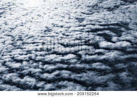 View of the white clouds from airplane window at night time.