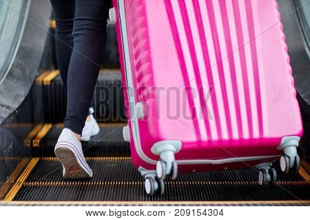 Girl raises a pink suitcase on an escalator close-up view from behind