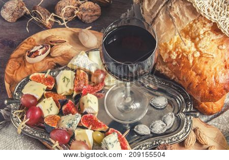 A glass of dry red wine and Italian Focaccia bread with cheese and a cheese platter with figs and Gorgonzola, brie, DorBlu and grapes. Selective focus. The horizontal frame.