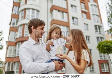 Cheerful parents holding their little daughter and keys to their new home in apartment building on the back. happy family outdoors.Loving family embracing posing in front of a new apartment building