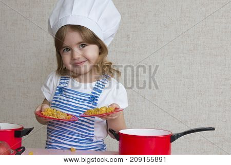 Portrait cute smiling chef cook girl enters the frame and standing at the kitchen table