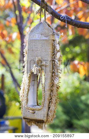 Vertical bird feeder. Feeding trough of burlap. A birdhouse with a chord.