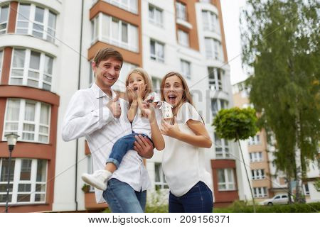 Young family looking excited moving into their new home screaming joyfully holding keys to their apartment.Attractive woman posing with her husband and daughter in front of a new apartment building