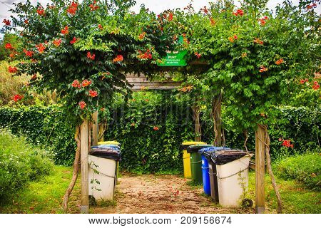 Trash cans for separate collection of garbage in summer park. Rural scene in Barcelona, Spain. Garbage containers and trees with colorful red flowers in garden. Plastic waste dumpsters in the town.
