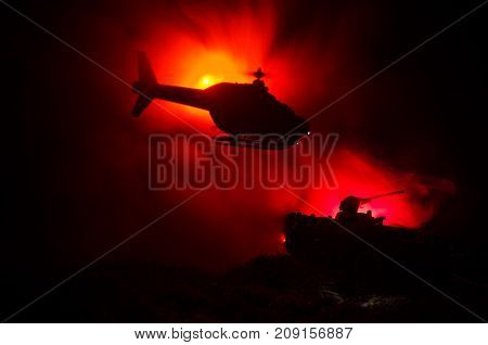 A Camouflaged Military Helicopter In Flight Against A Dramatic Red Sky. Heavy Armor In The Field Of