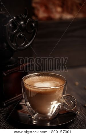 cup of coffee in coffee shop vintage color. Coffee grinder and Brown cane sugar on wooden table with flare blurred background. Retro style.