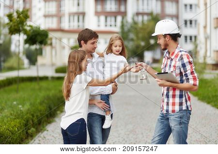 Real estate manager wearing protective helmet giving keys to a new home to a young happy family outdoors in front of apartment building. Buying new house concept happiness emotions bonding