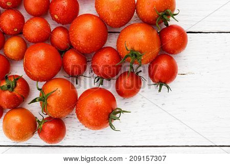 Many Wet Red  Tomatoes With Stalks On White Wood Board From Above. Space For Text.