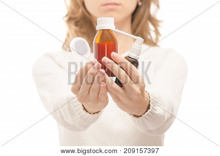 Woman in the hands of medicine syrup for throat spray on white background isolation
