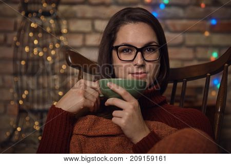Young woman sitting in rocking-chair enjoying hot tea at wintertime.