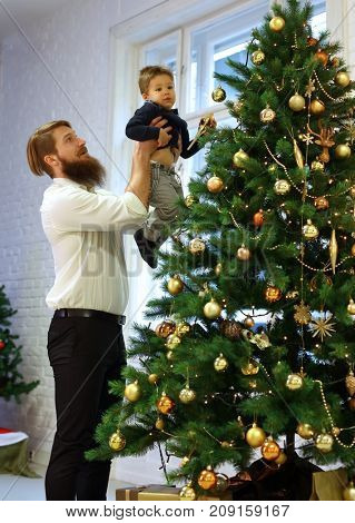 Father and little son decorating christmas tree at home, father holding boy in arms.