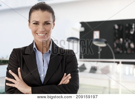Trusty female business professional smiling, standing arms crossed in modern office lobby.