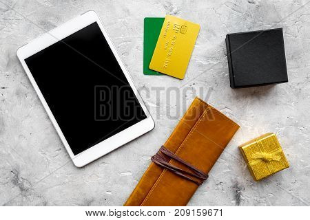 online payment for christmas present with credit card and tablet on gray stone table background top view mockup