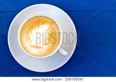 Cappuccino In White Ceramic Cup With Saucer On Blue Painted Wood From Above.