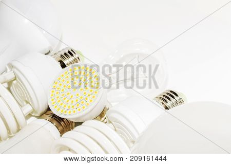 Several different led bulbs and compact fluorescent lamps with the size of the male screw base E27 on a light background