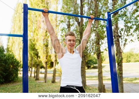 Workout, sportsman pull ups the horizontal bar