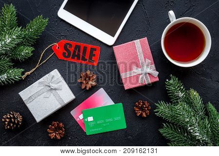 order new year 2018 present with sale with credit card and device on dark black table background top view mock up