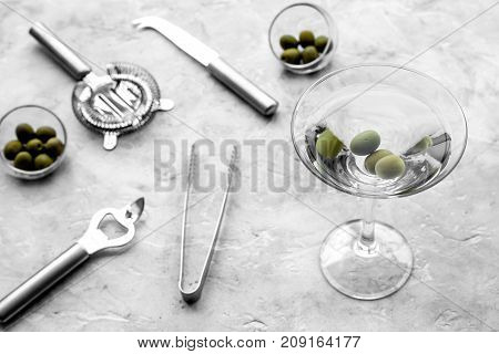 Make martini cocktails. Glass with beverage, olives and utensils on grey stone background top view.