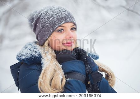 Cute young woman portrait playing with snow in warm woolen hat and coat in winter park.