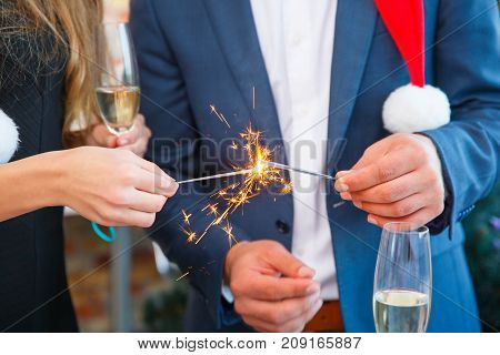 Close-up picture of festive man and woman cheering and clinking glasses on a blurred background. Colleagues lighting sparklers at the Christmas party.