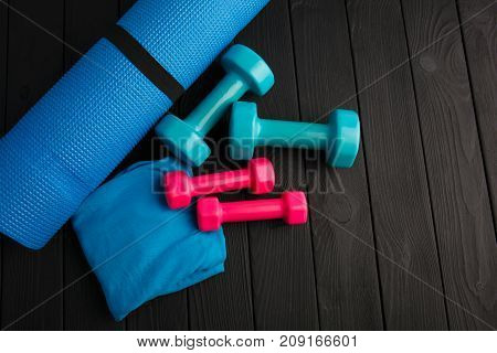 Dumbbells of blue and pink plastic on a brown wooden background. Health mode and fitness symbols. The concept of a healthy lifestyle and sport
