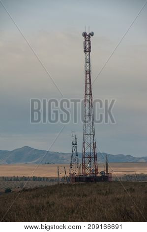 Telecommunications cell phone tower with antennas in a mountain location.