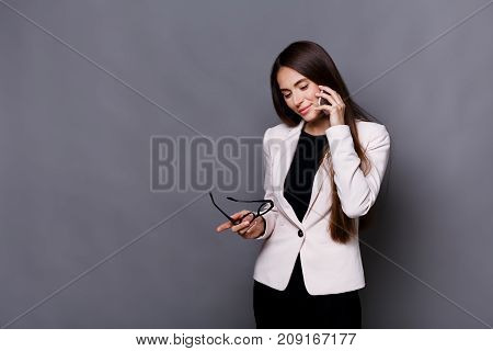 Thoughtful brunette woman speaks on mobile phone, make call and conversation concept. Copy space