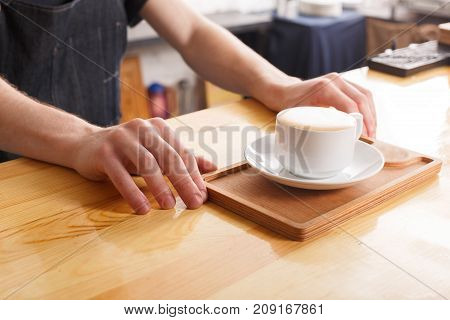 Unrecognizable barman serving freshly brewed cappuccino on wooden bar counter at modern coffee shop interior, copy space. Occupation people and service concept