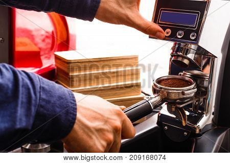 Barman making espresso in modern coffee machine. Closeup of male hand preparing bracing beverage. Small business and professional coffee brewing concept