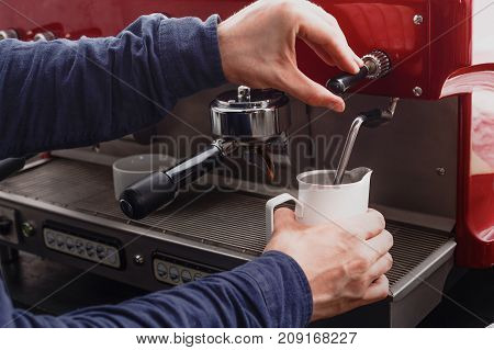Barman making cappuccino in modern coffee machine. Closeup of male hand steaming milk. Small business and professional coffee brewing concept