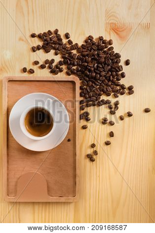 Coffee shop wooden counter background. Natural desk surface with espresso cup on tray and heap of coffee beans, top view with copy space. Small business concept, bar menu mockup